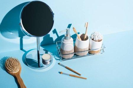 Photo pour Porte-brosses à dents avec articles d'hygiène, distributeur sur étagère de salle de bain avec miroir, brosse à cheveux, brosses cosmétiques sur fond bleu, concept zéro déchet - image libre de droit