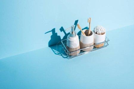 Photo pour Porte-brosses à dents avec écouteurs et brosses à dents avec distributeur savon liquide sur étagère de salle de bain sur fond bleu, concept zéro déchet - image libre de droit
