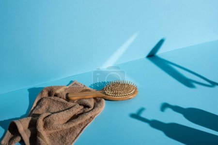 Hair brush on towel and shadows on blue background, zero waste concept