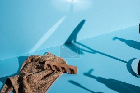 Foto de Comb on towel and shadows on blue background, zero waste concept - Imagen libre de derechos