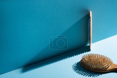 Photo pour Peigne et brosse à cheveux sur fond bleu, concept zéro déchet - image libre de droit
