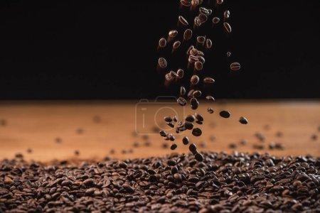 Photo pour Grains de café torréfiés tombant sur une pile sur fond noir - image libre de droit