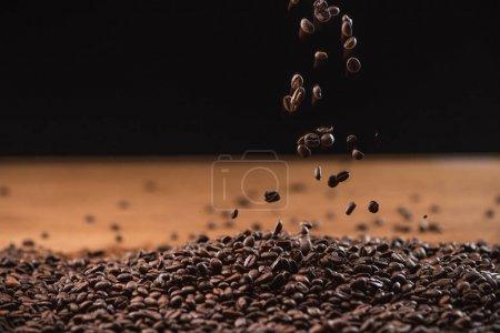 Photo pour Grains de café torréfiés tombant sur pile sur fond noir - image libre de droit