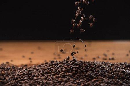 Photo pour Grains de café frais torréfiés tombant sur pile sur fond noir - image libre de droit