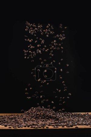 Foto de Granos de café tostados en la pila y en el aire aislados en negro - Imagen libre de derechos