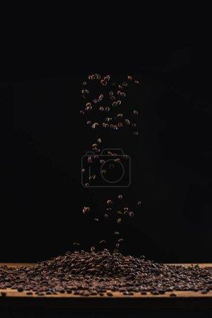 Photo pour Grains de café torréfiés en pile et dans l'air isolé sur noir - image libre de droit