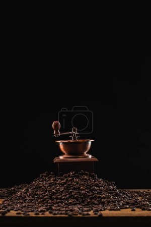 Photo for Coffee grinder on fresh roasted coffee beans isolated on black - Royalty Free Image
