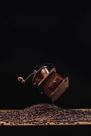Photo pour Broyeur de café au-dessus de grains de café torréfié frais isolé sur noir - image libre de droit