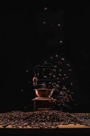 coffee grinder and fresh roasted coffee beans in air isolated on black