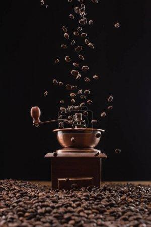 Photo pour Broyeur de café et grains de café torréfiés frais à l'air isolé sur noir - image libre de droit