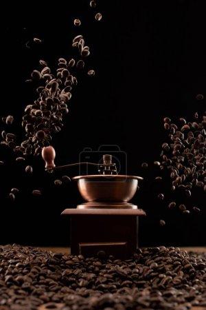 Photo pour Moulin à café et grains de café frais torréfiés dans l'air isolé sur noir - image libre de droit