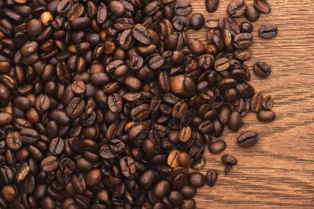 Photo for Top view of fresh roasted coffee beans on wooden surface - Royalty Free Image