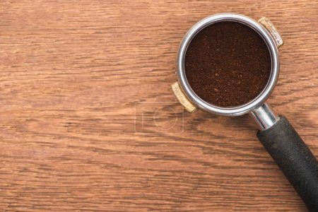 Foto de Top view of fresh roasted coffee beans and ground coffee in filter holder on wooden table - Imagen libre de derechos