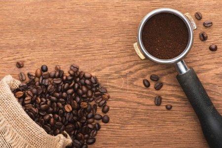 Photo pour Vue de dessus de grains de café torréfiés frais éparpillés dans des sacs et du café moulu dans un porte-filtre sur table en bois - image libre de droit
