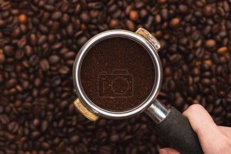 cropped view of woman holding ground coffee in filter holder above fresh roasted coffee beans