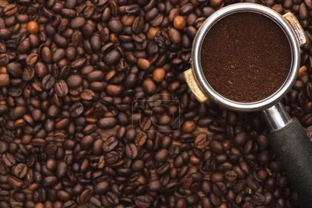 Photo for Top view of ground coffee in filter holder on fresh roasted coffee beans - Royalty Free Image
