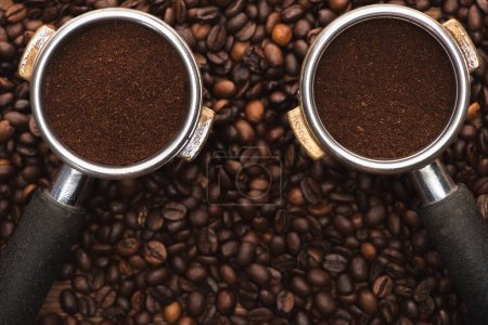 Photo for Top view of fresh roasted coffee beans and ground coffee in filter holder on wooden table - Royalty Free Image