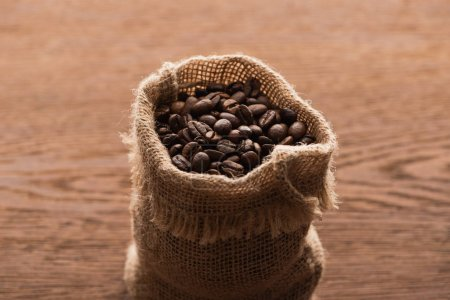 Photo for Fresh roasted coffee beans in sack on wooden table - Royalty Free Image