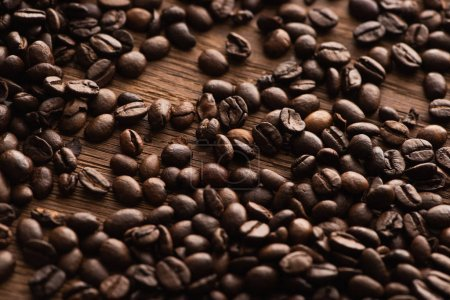 Photo for Fresh roasted coffee beans scattered on wooden table - Royalty Free Image
