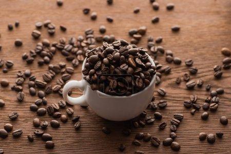 Photo pour Focalisation sélective de la tasse de grains de café torréfiés frais sur une table en bois - image libre de droit