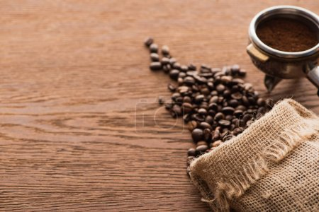 Photo for Fresh roasted coffee beans and ground coffee in filter holder on wooden table - Royalty Free Image