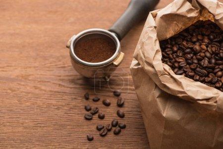 Photo pour Café torréfié frais dans un sac en papier et café moulu dans un porte-filtre sur table en bois - image libre de droit