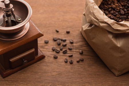 Photo for Selective focus of fresh roasted coffee beans in paper bag near coffee grinder on wooden table - Royalty Free Image