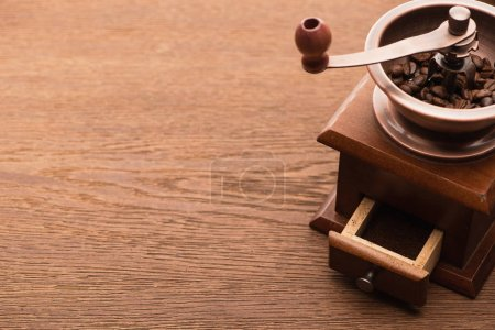 Photo for Fresh roasted coffee beans in coffee grinder on wooden table - Royalty Free Image