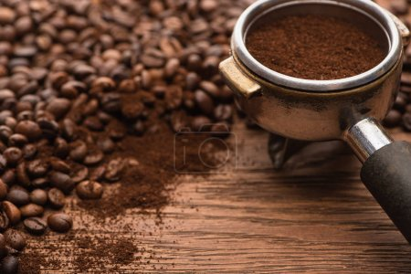 Photo pour Mise au point sélective de grains de café frais torréfiés et de café moulu dans un porte-filtre sur table en bois - image libre de droit