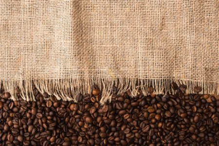 Photo for Top view of fresh roasted coffee beans and sackcloth - Royalty Free Image