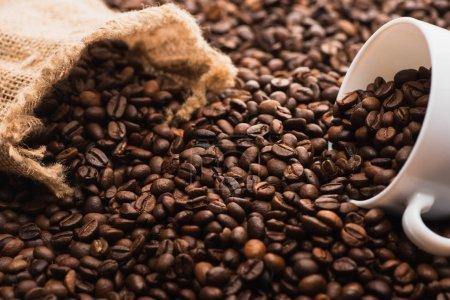 Photo pour Focalisation sélective des grains de café torréfiés frais et de la tasse blanche près du sac - image libre de droit