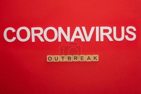 Photo pour Vue en haut du lettrage coronavirus et épidémie sur cubes de bois sur fond rouge - image libre de droit