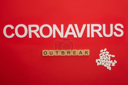 Top view of lettering coronavirus and outbreak on wooden cubes near pills on red background