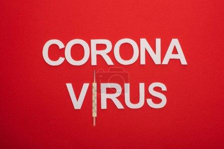 Photo pour Vue du dessus du lettrage du coronavirus avec thermomètre isolé sur rouge - image libre de droit