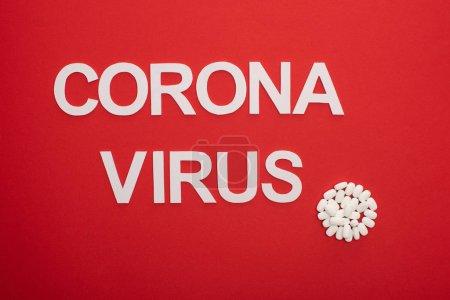 Vue du dessus des pilules et du lettrage du coronavirus sur fond rouge