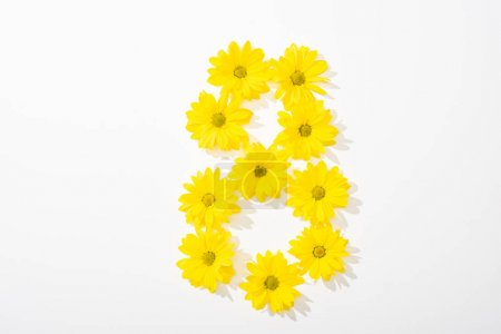 Photo for Top view of yellow daisies arranged in number 8 on white background - Royalty Free Image