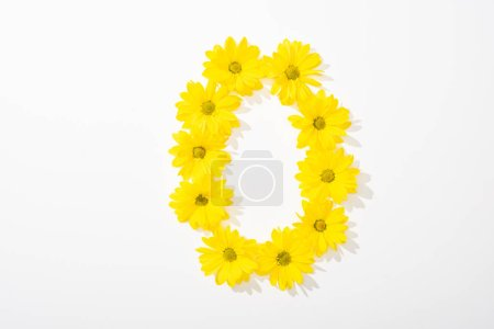 Photo for Top view of yellow daisies arranged in number 0 on white background - Royalty Free Image