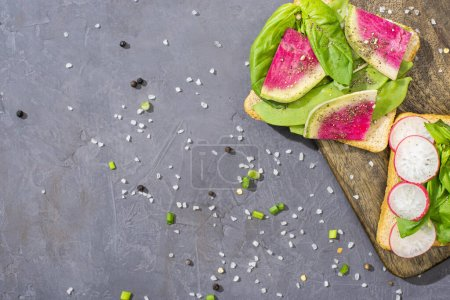 Photo for Top view of tasty fresh sandwiches with vegetables on wooden board with pepper and salt - Royalty Free Image