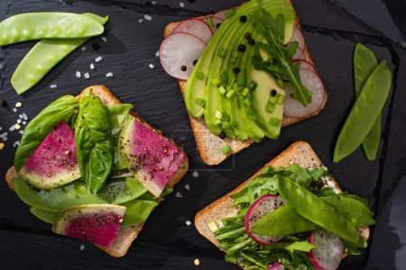 Photo pour Top view of healthy toasts with raw vegetables with pepper seeds and salt - image libre de droit
