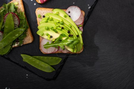 Photo for Top view of fresh sandwiches with radish and avocado on stone board with pepper and salt - Royalty Free Image