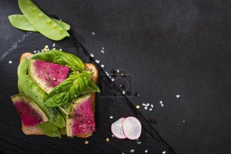 vista superior del sándwich de rábano orgánico en la tabla de cortar piedra con semillas de pimienta y sal