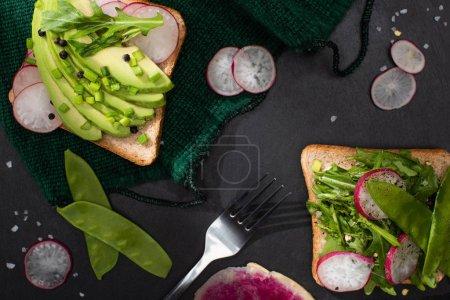 Foto de Vistas superiores de sándwiches vegetarianos sanos con rábano, guisantes verdes y aguacate sobre tela con tenedor. - Imagen libre de derechos
