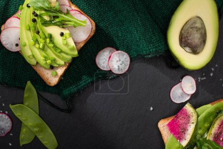Photo for Top view of fresh toasts with radish, green peas, leek and avocado on green cloth - Royalty Free Image