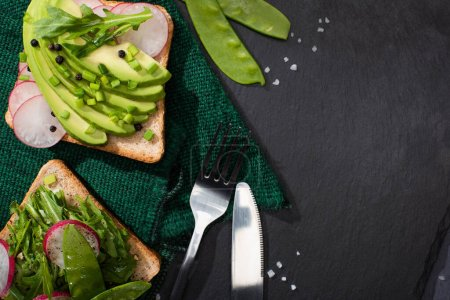 Photo for Top view of vegetarian organic toasts with fresh vegetables on cloth with fork and knife - Royalty Free Image