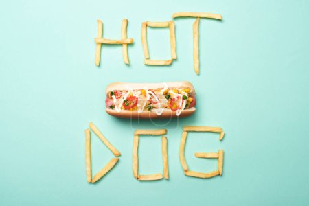 Photo pour Top view of american hot dog on blue with word hot dog made from french fries - image libre de droit