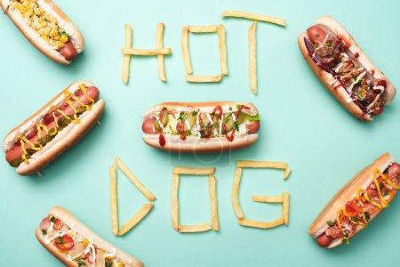 Photo pour Vue du dessus de hot dogs malsains sur bleu avec mot hot dog à base de frites - image libre de droit