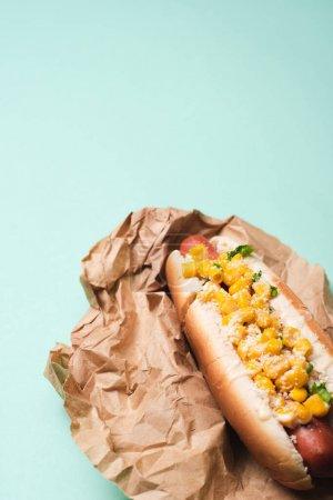 Photo pour Délicieux hot dog avec du maïs sur papier bleu - image libre de droit