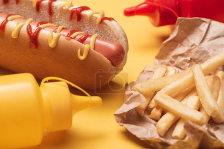 tasty hot dog, french fries in paper and bottles with ketchup and mustard on yellow