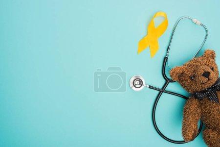 Photo pour Vue du ruban jaune, jouet et stéthoscope sur fond bleu, concept de la Journée internationale du cancer chez les enfants - image libre de droit