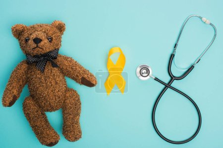 Photo for Top view of yellow awareness ribbon, teddy bear near stethoscope on blue background, international childhood cancer day concept - Royalty Free Image